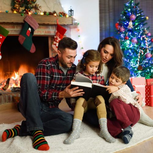 Young couple reading a book with children in their living room decorated for Christmas